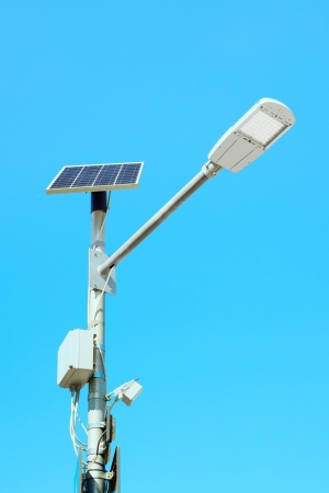 lamp posts: Solar panel cell powered street light lamp on a blue sky background