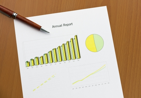 Annual report chart histogram, lines and area  Ink color print paper and a pen on wooden desk  Monthly stats  Stock Photo - 16062366
