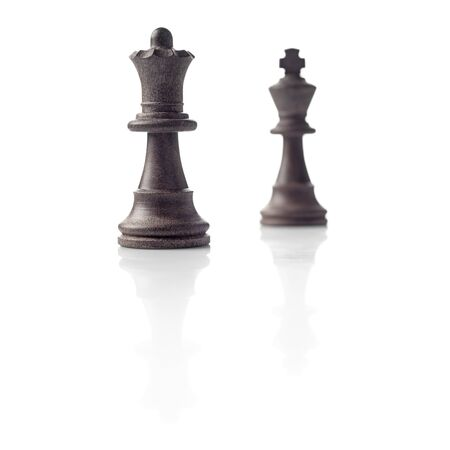 Chess  Black Queen and King out of focus and their shadows reflection on white background  Winner, power, competition or leadership men women concept  photo