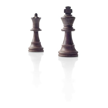 Chess  Black King and Queen out of focus and their shadows reflection on white background  Winner, power, competition or leadership men women concept  photo