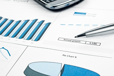 listing: Annual growth report chart histogram, lines and pie close up  Ink color print paper, pen and smartphone  Monthly stats  Stock Photo