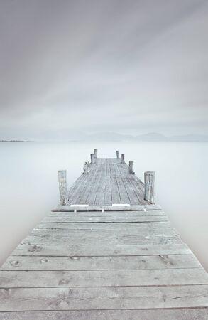 Träbrygga i en grumlig och dimmig humör En lång exponering fotografi taget i höst Stockfoto