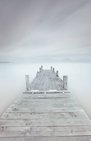 Wooden pier in a cloudy and foggy mood  A long exposure photography taken in autumn  Stock Photo - 16682472
