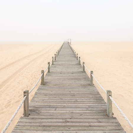 rope bridge: Wooden footbridge on a foggy sand beach  Figueira da Foz, Portugal, Europe  Stock Photo