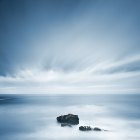 moody sky: Dark rocks in a blue ocean under cloudy sky in a bad weather  Long exposure photography Stock Photo