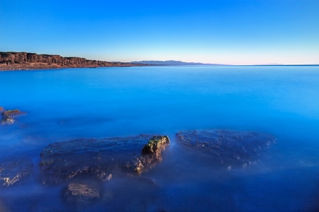 crepuscle: Submerged rocks in a blue ocean, under a clear sky on a bay beach on sunset  Pine forest on background coast  Maremma, Tuscany, Italy Stock Photo