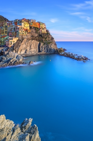 Manarola town on cliff rocks and sea at sunset , Seascape in Five lands, Cinque Terre National Park, Liguria Italy Europe  Long Exposure Photography  photo