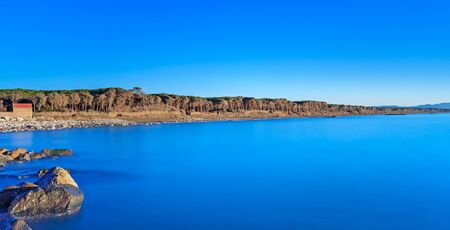 crepuscle: Blue ocean, rocks, pine forest on background, clear sky and beach on sunset  Panoramic seascape in Maremma, Tuscany, Italy  Long exposure photography Stock Photo