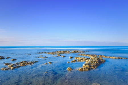 Rocks in a blue ocean under a clear sky on sunrise at morning  Tuscany, Italy  Long exposure photography Stock Photo - 17153384