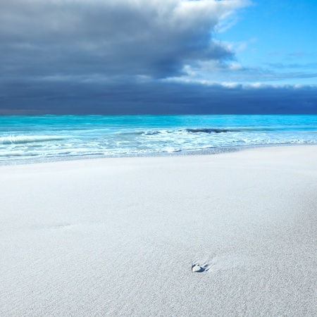 Ocean seascape  White rock or pebble in a white sandy beach under blue cloudy sky in a bad weather  Waves on background Stock Photo - 17186233