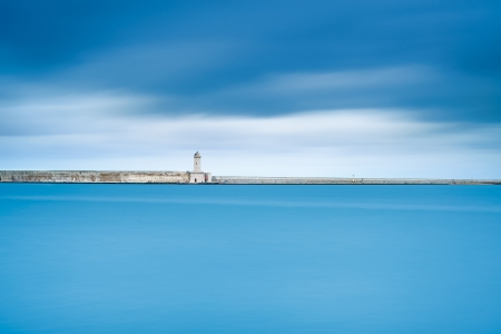 Livorno port lighthouse, breakwater and soft water under cloudy sky  Tuscany, Italy, Europe  Long exposure photography  Stockfoto