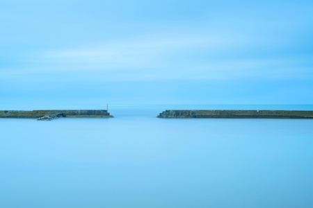 Concrete pier and stairs in a cloudy and blue ocean  A long exposure photography taken in autumn  photo