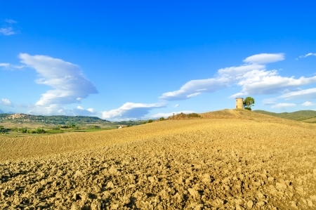 Tuscany, Maremma typical countryside landscape with rolling hills, rural tower, plowed field and village on background  photo
