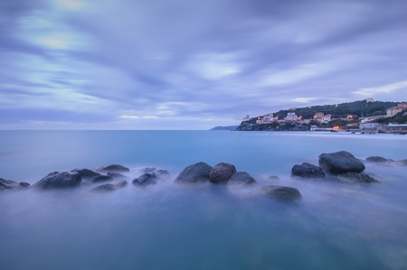 crepuscle: Dark Rocks in a blue ocean on twilight  Castiglioncello, Tuscany, Italy  Long exposure photography