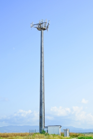 Telecommunications tower  Mobile phone base station in a blue sky background  photo