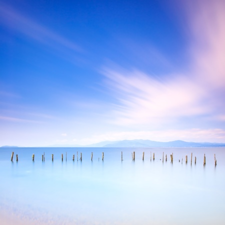 serenity: Fishing poles and soft water on a quiet sea landscape  Long exposure photography Stock Photo