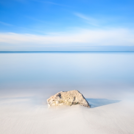 A rock on a white sand beach and blue ocean on horizon  Long exposure photography  photo
