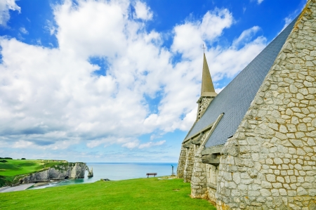 garde: Church Notre Dame de la Garde chapel, Etretat village, its bay beach and Aval cliff landmark  Aerial view  Normandy, France, Europe