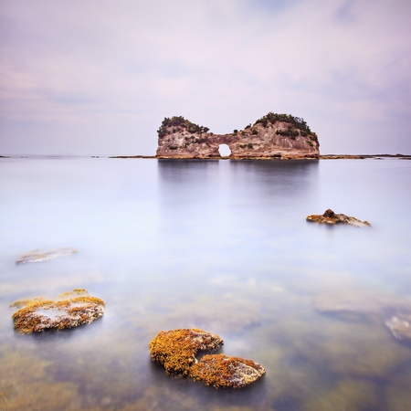 Hole island and rocks in a tropical blue ocean  Cloudy sky  Long exposure photography Stock Photo - 17811064