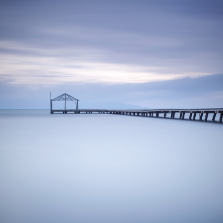 winterday: Wooden pier or jetty silhouette in a blue ocean on sunset  Long exposure photography taken in autumn in a italian beach Stock Photo