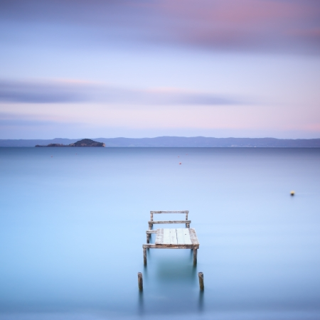 Wooden pier or jetty on a blue lake  Hills on background  Long exposure photography in Bolsena lake, Italy, Europe