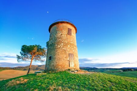 crepuscle: Tuscany, Maremma typical countryside sunset twilight landscape with hills, tree and rural tower  Stock Photo