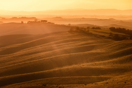 Tuscany, rolling hills on sunset  Crete Senesi rural landscape and sunlight  Green fields, a farm with trees  Siena, Italy photo