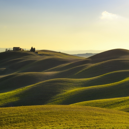 hills land: Tuscany, rural landscape in Crete Senesi land  Rolling hills, countryside farm, cypresses trees, green field on warm sunset  Siena, Italy, Europe  Stock Photo