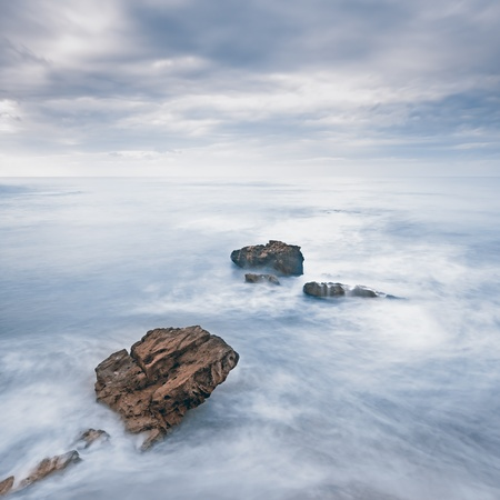Rocks in a blue ocean waves under cloudy sky in a bad weather\ Long exposure photography