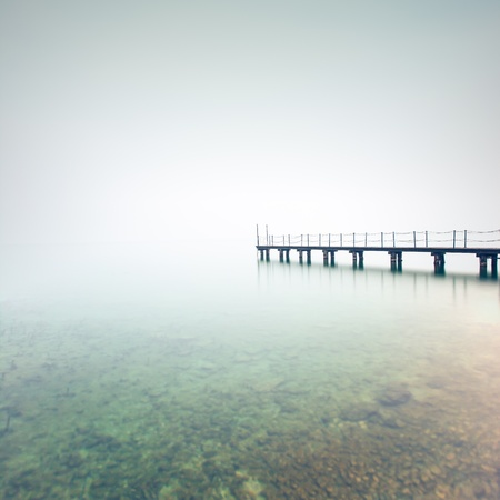 garda: Pier or jetty silhouette in a foggy lake  Garda lake, Italy, Europe Stock Photo