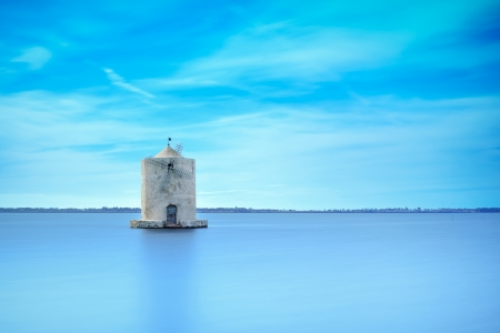 Old spanish windmill in a blue lagoon  Molino spagnolo landmark Orbetello, Monte Argentario, Tuscany, Italy  Long exposure photography