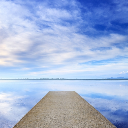 peaceful background: Concrete pier or jetty and on a blue lake and cloudy sky reflection on water