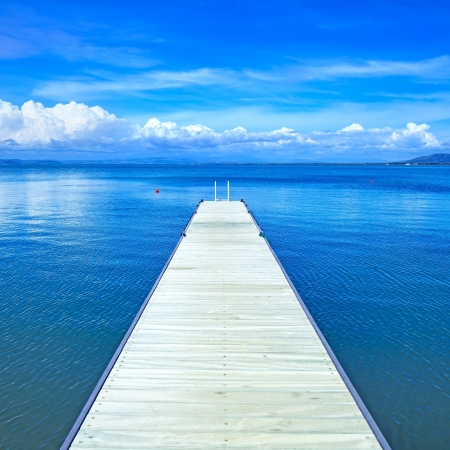 Wooden pier or jetty on a blue ocean and clear sky  Bay beach in Monte Argentario, Porto Santo Stefano, Tuscany, Italy photo