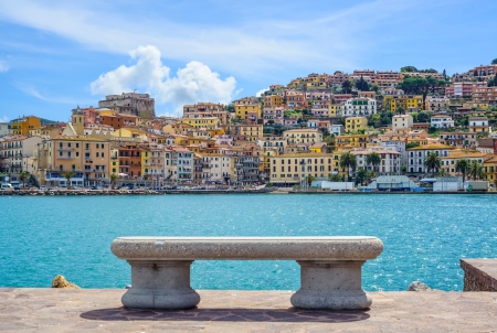 Bench on seafront in Porto Santo Stefano harbor, Monte Argentario, Tuscany, Italy  Stock Photo
