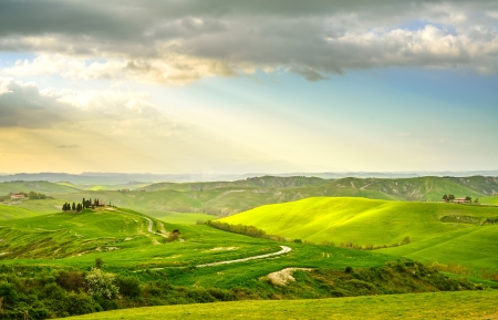 Tuscany, rural sunset landscape  Countryside farm, cypresses trees, green field, sun light and cloud  Volterra, Italy, Europe  Imagens