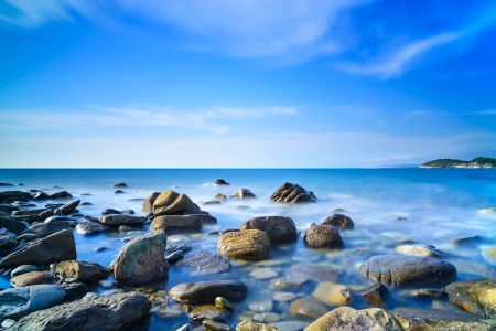 panoramic beach: Baratti bay, rocks in a blue ocean under a clear sky on sunset  Tuscany, Italy