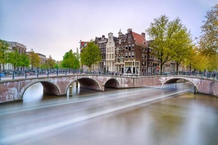 アムステルダム橋と水の運河ボート夕日のオランダやオランダ ヨーロッパに長時間露光で光跡