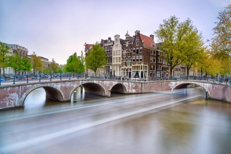 amsterdam canal: Amsterdam  Bridge and water canal  Boat light trail in long exposure on sunset  Holland or Netherlands  Europe