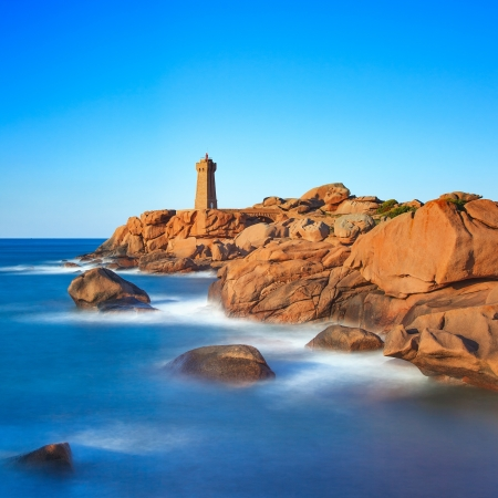 Ploumanach Mean Ruz lighthouse red sunset in pink granite coast, Perros Guirec, Brittany, France  Long exposure  photo