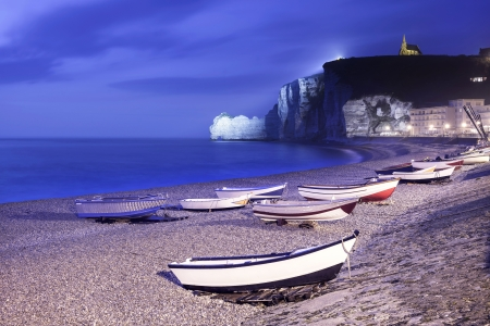 crepuscle: Etretat village, bay beach and boats on a foggy night  Normandy, France, Europe