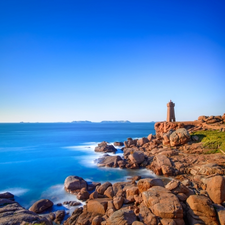 Ploumanach Mean Ruz lighthouse red sunset in pink granite coast, Perros Guirec, Brittany, France  Long exposure