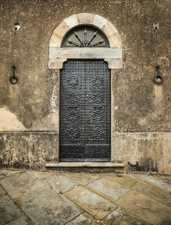 Traditional old vintage iron door and grunge wall in Tuscany, Italy, Europe  photo