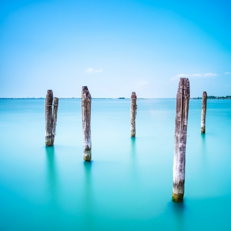 Poles and soft water on Venice lagoon  Long exposure photography  Imagens