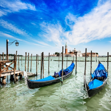 Venice, gondolas or gondole on a blue sky and San Giorgio Maggiore church landmark on background  Italy, Europe  photo