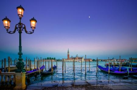Venetië, straatlantaarn en gondels of gondole op een blauwe zonsondergang schemering en San Giorgio Maggiore kerk landmark op de achtergrond Italië, Europa Stockfoto