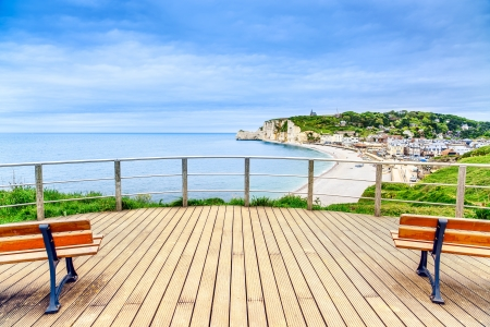 Etretat panoramic view landmark, balcony, beach and village under a cloudy sky  Normandy, France, Europe  photo