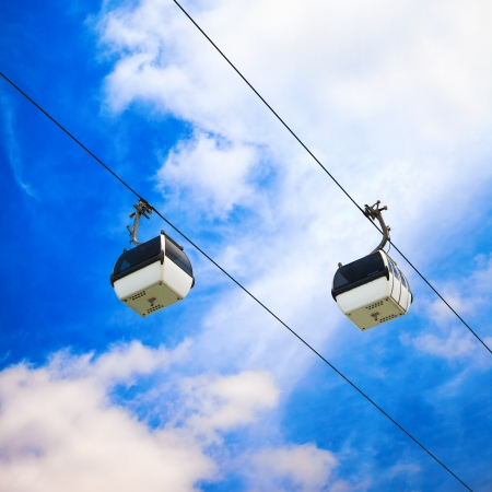 cableway: A cablaway with two cable car on a partly cloudy blue sky background