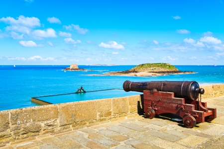 ramparts: Old cannon along  Saint Malo wall ramparts and fort on background  View to Dinard  Brittany, France, Europe