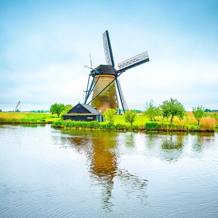 Windmill and water canal reflection in Kinderdijk, Holland or Netherlands