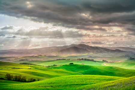 Tuscany, rural sunset landscape  Countryside farm, cypresses trees, green field, sun light and cloud  Volterra, Italy, Europe  Stock Photo